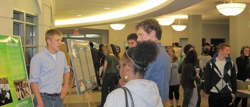 Group of attendees speaking to a poster presenter at the 2011 Hightower Symposium