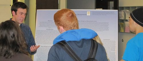 Poster presenter, Quentin Reynolds of the Anthropology and Sociology department, explaining his poster to three students at the 2011 Hightower Syposium.