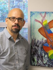 Francisco Villegas standing next to abstract artwork